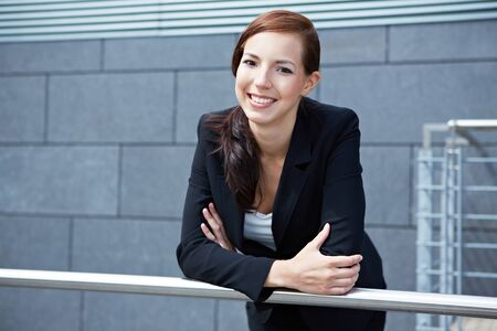 Happy smiling business woman leaning on a railing photo