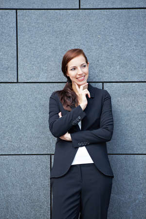Attractive pensive business woman leaning on wall Stock Photo - 14903287