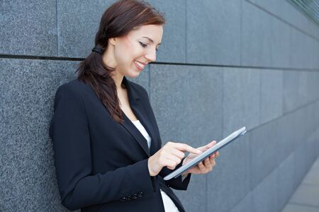 Urban business woman using tablet computer while leaning on wall photo