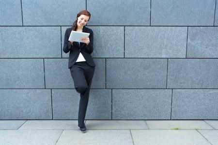 sozialarbeit: Gl�ckliche Gesch�ftsfrau mit Tablet PC lehnt an einer Wand