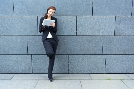 business woman: Happy businesswoman with Tablet PC leaning on a wall Stock Photo