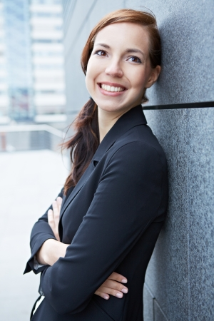 Happy confident business woman leaning on wall in the city photo