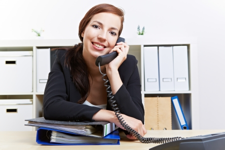 Attractive happy business woman making a phone call in her office photo
