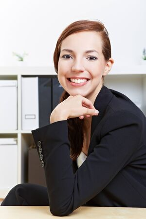 Smiling confident business woman sitting in the office at her desk photo