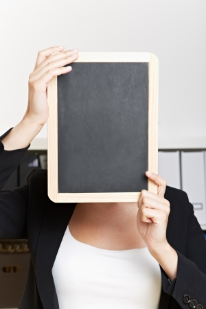 Empty chalkboard in front of face of business woman in her office photo