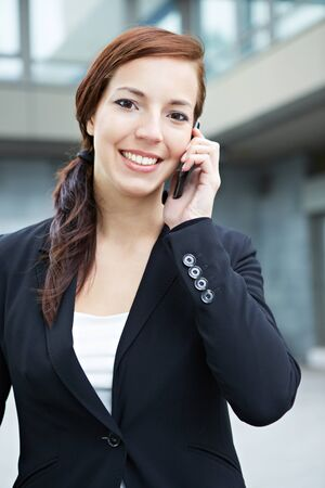 Attractive business woman making a phone call in the city photo