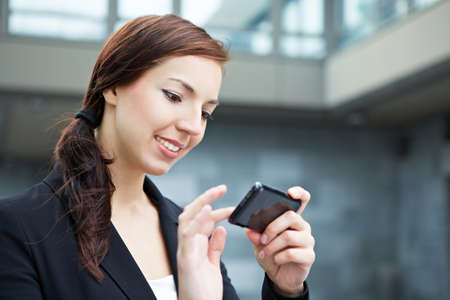 Attractive young woman using her smartphone on the way in the city photo