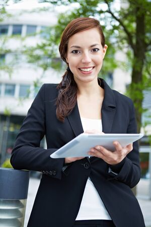 Happy business woman with tablet computer in the city Stock Photo - 14903303