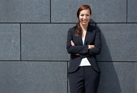 Attractive happy business woman with her arms crossed leaning on wall photo