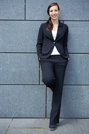 Content happy business woman in city leaning on wall Stock Photo - 14903320