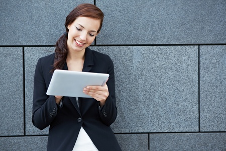 app: Smiling businesswoman working on tablet computer leaning on a wall Stock Photo