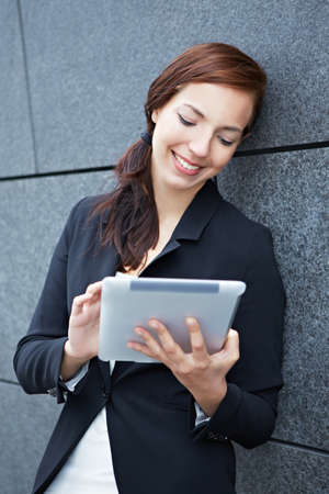 Mobile business woman working with tablet PC in the city photo