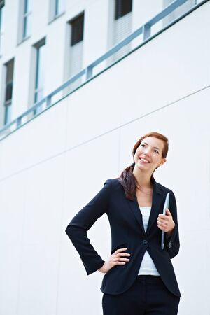 Happy business woman standing in front of a university photo