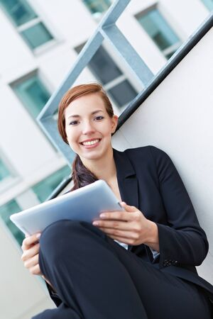 Happy female student working on tablet computer in university Stock Photo - 14903311