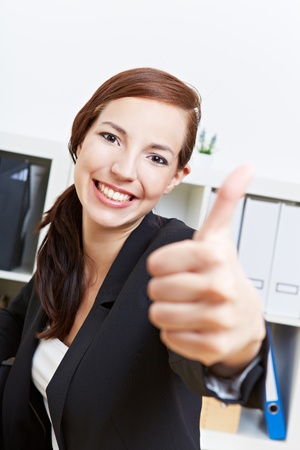 place of work: Happy businesswoman holding her thumbs up in the office Stock Photo