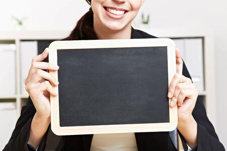 Happy business woman holding small black chalkboard photo