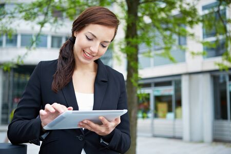 Attractive business woman using tablet computer on the way in the city Stock Photo - 14961888