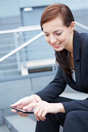 Young business woman sitting on stairs using a smartphone Reklamní fotografie