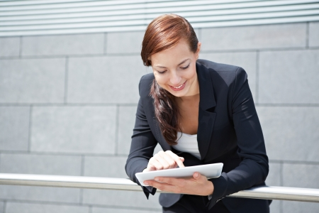 Attractive smiling businesswoman with tablet computer on the way photo