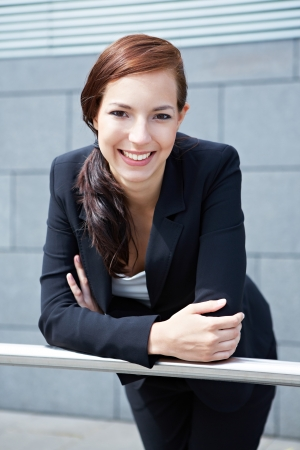 Happy young business woman smiling on a railing photo