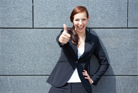 Happy smiling business woman in city holding her thumbs up photo