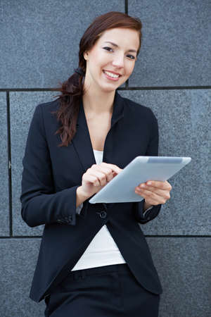 Business woman with digital tablet computer leaning on wall Stock Photo - 14961912