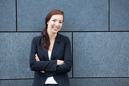 Happy business woman with her arms crossed leaning on a wall photo