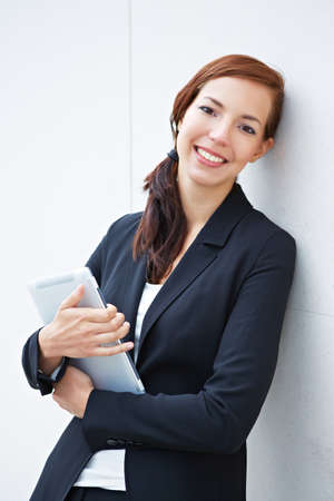 Smiling attractive business woman holding a tablet computer in her arms photo