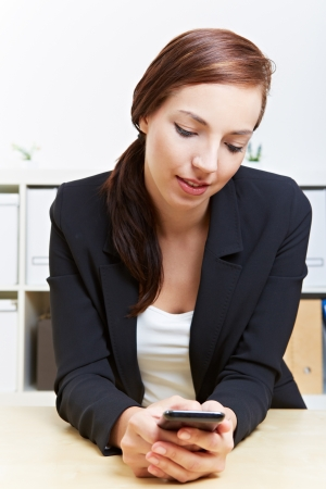 Attractive business woman using smartphone in the office at her desk photo