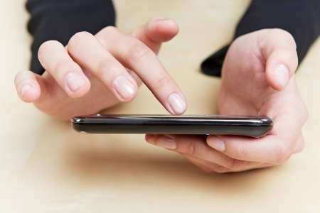 Index finger touching the screen of a smartphone Stock Photo - 14961877
