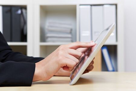 Two hands holding tablet PC in the office on a desk photo