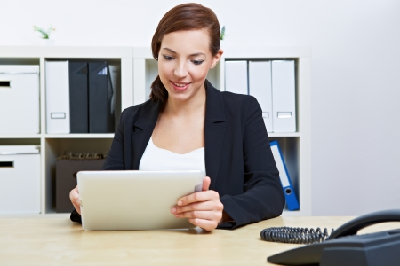 Business woman sitting in her office using a tablet computer Stock Photo - 14961878