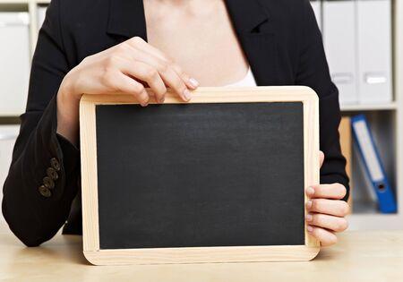 Hands holding empty black slate chalkboard in office photo