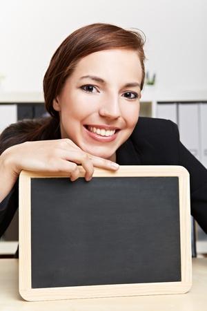 Happy business woman showing empty black chalkboard photo