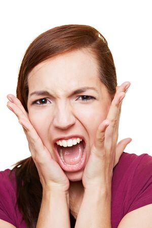 Young attractive woman screaming loudly with hands on her cheeks photo