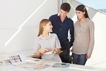 designers interior: Donna sorridente sta consultando giovane coppia per un consiglio colore