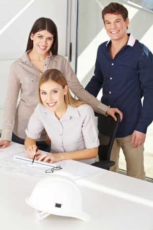 architectural firm: Three happy architects with construction drawing in their office Stock Photo