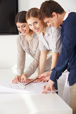 architectural firm: Three smiling architects working with a blueprint in their office