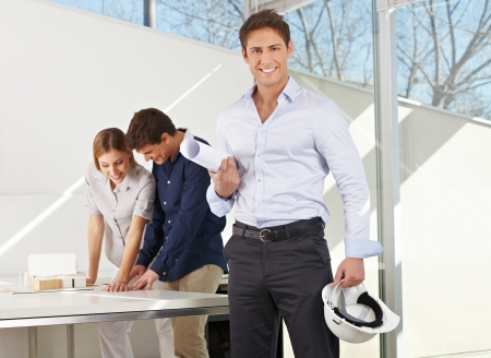 architectural firm: Happy architect with construction plan and helmet in his office Stock Photo