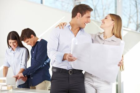 architectural firm: Happy couple with building plan for their new house in architecture office