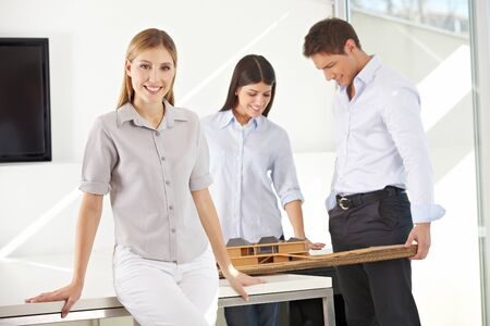 architectural studies: Female smiling architect with her team in the office