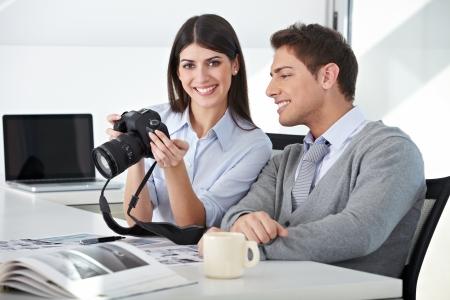 stock agency: Fotografo con assistente alla macchina che tiene in ufficio