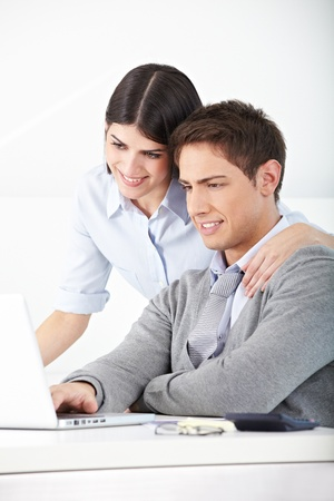 Man and woman in an office looking at laptop computer photo