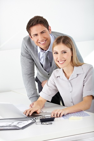 Happy man and woman working together with laptop computer in an office Stock Photo - 15446939