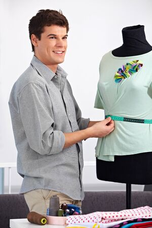 Man working as fashion designer with dress doll in his studio Stock Photo - 15451033