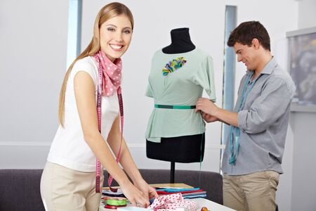 alteration shop: Smiling happy fashion designer in studio wotking with dress form Stock Photo