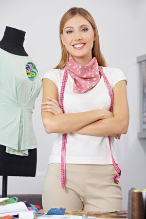 alteration shop: Smiling fashion designer with tape measure and her arms crossed Stock Photo