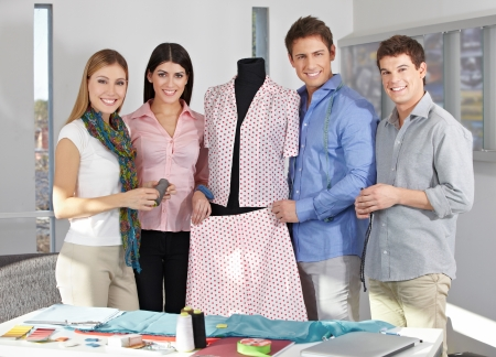 Happy Fashion design team in a studio around a dress form photo