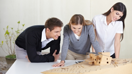 architectural studies: Three architects in office looking at 3D building model Stock Photo