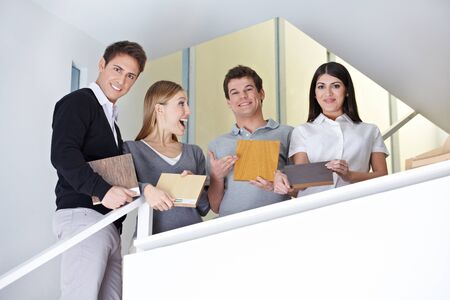 Happy group of sales representatives holding different parquet floor samples photo